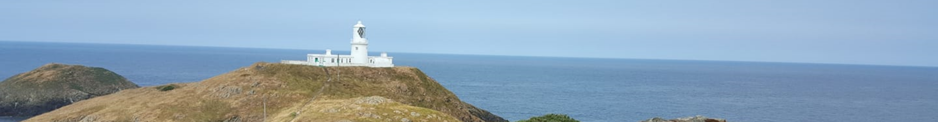 A landscape image of the sea with a lighthouse